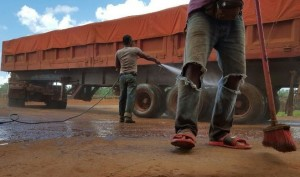 Locals clean a truck used for hauling bauxite in Kuantan. Photo Credit: Media Corp