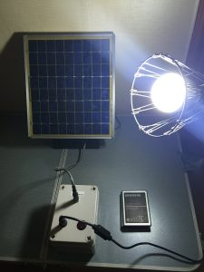 The researcher's prototype system consisting of a solar panel and a LED lamp wired to a battery pack containing three Samsung Galaxy Note 2 batteries. Photo Credit: Boucar Diouf/Kyung Hee University