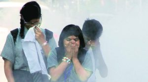 Students cover their mouths from extensive air pollution on the street. Photo Credit: Flickr