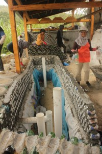 Many hands make light work as glass bottles are carefully laid, minimizing the use of environmentally-taxing cement.
