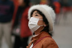 A woman protects herself from air pollution on the street. Photo Credit: Flickr