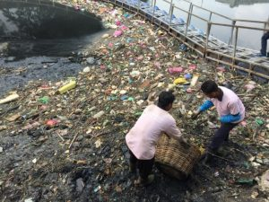 Two municipal workers are trying to clean up waste that clogs up Sungai Pinang on Penang. Photo Credit: Sinar Online