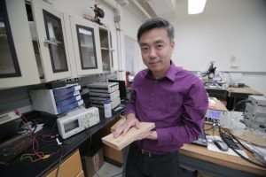 Material scientist Xudong Wang holds a prototype of a new piece of energy harvesting technology, which uses wood pulp and harnesses nanofibers. Photo Credit: Stephanie Precourt