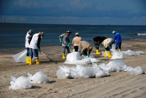 Volunteers help clean up a beach. Nothing should stop us from engaging in similar initiatives. Photo Credit: Wikimedia Commons